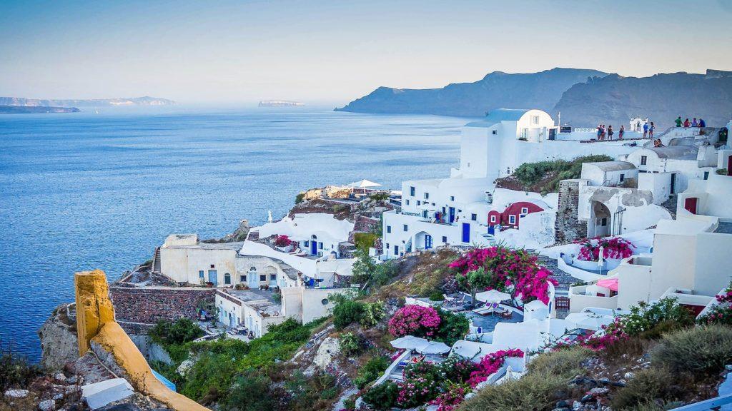 Griechenlands Küste mit seinen weißen gebäuden und violetten Blumenfarben ist traumhaft