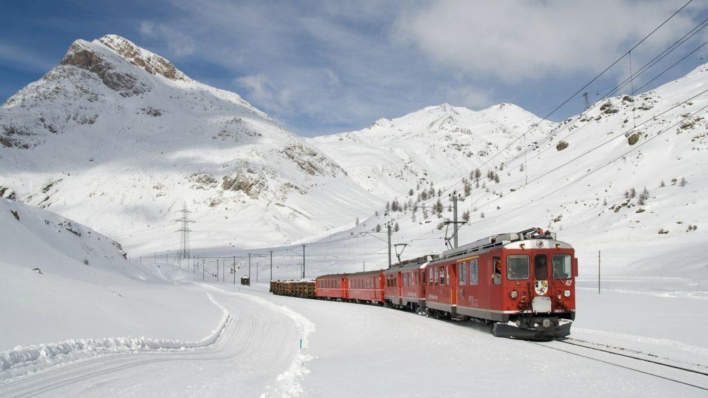 Schweizer Eisenbahn fährt durch schneebedeckten schweizer Alpen