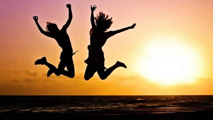 Fröhliche, in die Luft springende junge Menschen am Strand